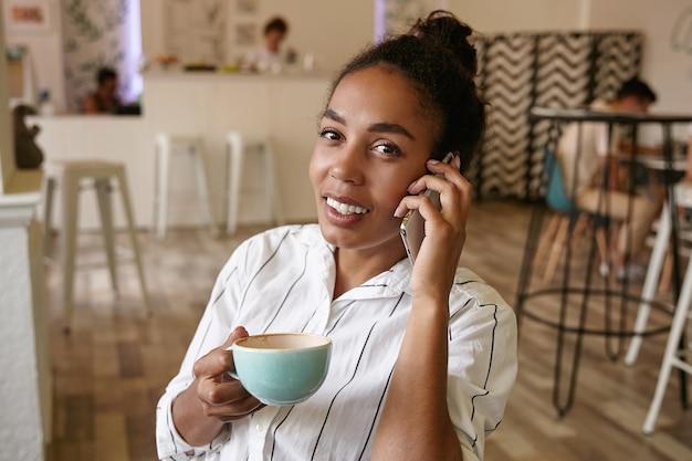 Mooie donkere vrouw in vrijetijdskleding op zoek met charmante glimlach, kopje koffie houden en bellen met haar smartphone