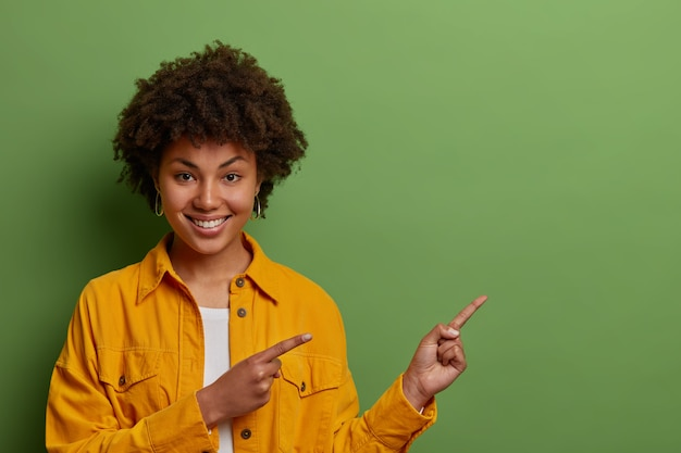 Mooie donkere vrouw met afro-haar wijst voor de vingers naar rechts, suggereert deze richting te gaan, demonstreert geweldig product, draagt gele jas,