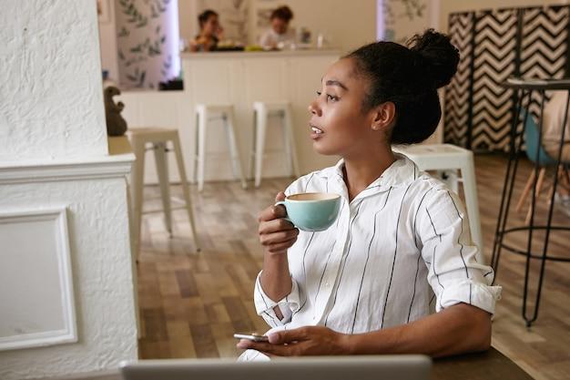 Mooie donkere vrouw met een kopje koffie in de hand, bedachtzaam opzij kijken en mobiele telefoon vasthouden, poseren boven café interieur