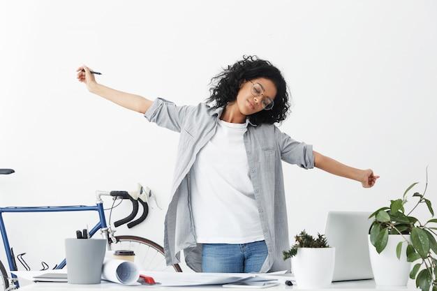 Mooie donkere vrouw met een vermoeide uitdrukking na hard werken op kantoor, gevoel ontspannen uitrekken