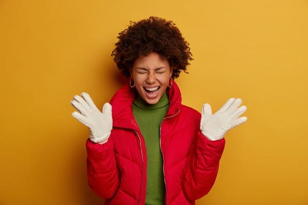 Mooie donkere vrouw met krullend haar, draagt winterbovenkleding, witte handschoenen, drukt geluk uit, roept uit van plezier, geïsoleerd over gele studiomuur.