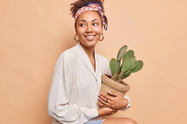 Mooie donkere vrouw met krullend haar zit en kijkt vrolijk weg houdt pot of stekelige sappige cactus