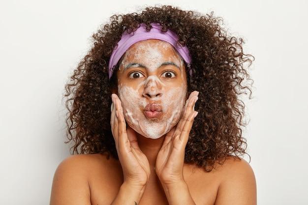 Mooie donkere vrouw trekt een grappig gezicht, houdt de lippen gevouwen, raakt de wangen met beide handpalmen, wast het gezicht met zeep, staat naakt binnen, geniet van dagelijkse hygiënische procedures. verwennerij concept
