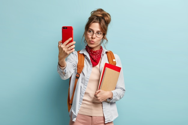 Mooie donkerharige blanke vrouw maakt selfie portret met mobiele telefoon, lippen gevouwen houdt, notebook en rugzak draagt op rug