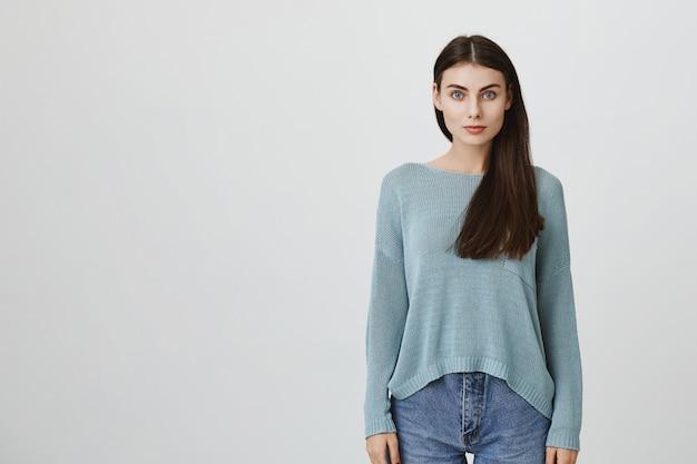 Mooie donkerharige jonge vrouw in blauwe losse trui en jeans