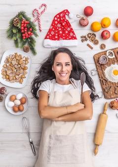 Mooie donkerharige kok die op de grond ligt en breed lacht, de houten lepel vasthoudt en wordt omringd door peperkoeken, eieren, meel, kerstmuts en fruit.