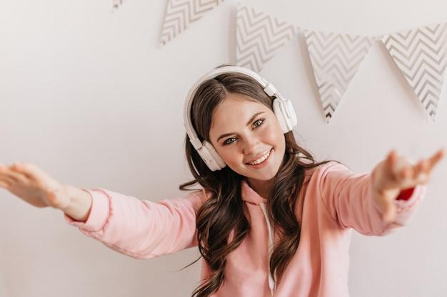 Mooie donkerharige vrouw in roze hoodie en enorme witte koptelefoon poseren in lichte appartementen