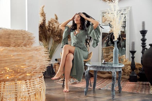 Mooie donkerharige vrouw in sjamanistische etnische outfit in bali-stijl ingerichte kamer