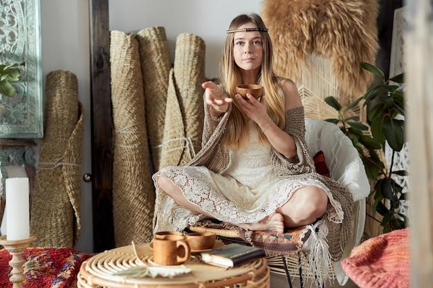Mooie donkerharige vrouw in sjamanistische etnische outfit in bali-stijl ingerichte kamer Premium Foto