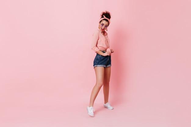 Mooie donkerharige vrouw in verband op haar hoofd en lila bril poseren op geïsoleerde ruimte. portret van meisje in witte sneakers, korte broek en shirt.