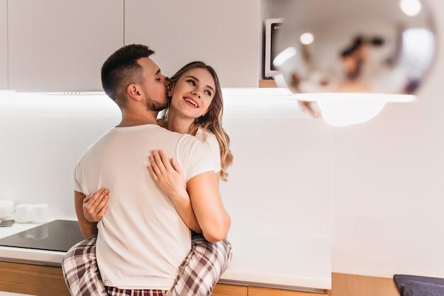 Mooie donkerharige vrouw met plezier met echtgenoot in de keuken. brunette mannelijk model in wit t-shirt poseren met vriendin voor het ontbijt.