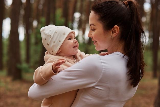 Mooie donkerharige vrouw met witte kleding die buiten poseert, baby baby in handen houdt en met grote liefde naar dochter kijkt, spelend in het bos