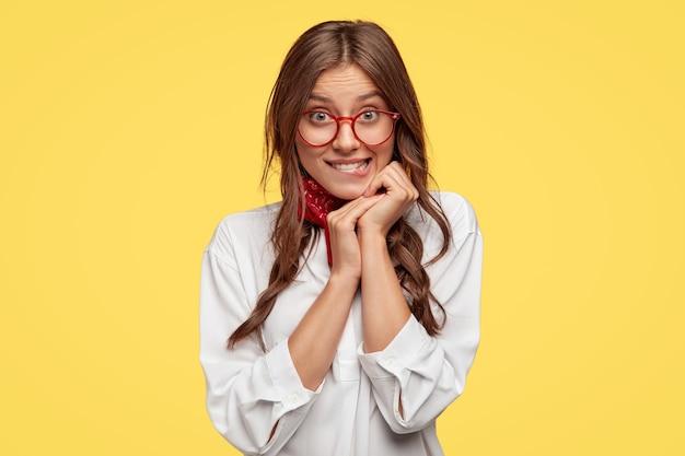 Mooie donkerharige vrouw voelt verleiding, bijt onderlip, kijkt met veel verlangen, houdt handen dicht bij gezicht, draagt een oversized wit overhemd, modellen tegen gele muur, heeft bril met rode randen