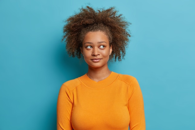 Mooie doordachte afro-amerikaanse vrouw met krullend haar gezonde donkere huid kijkt opzij denkt diep casual trui draagt.