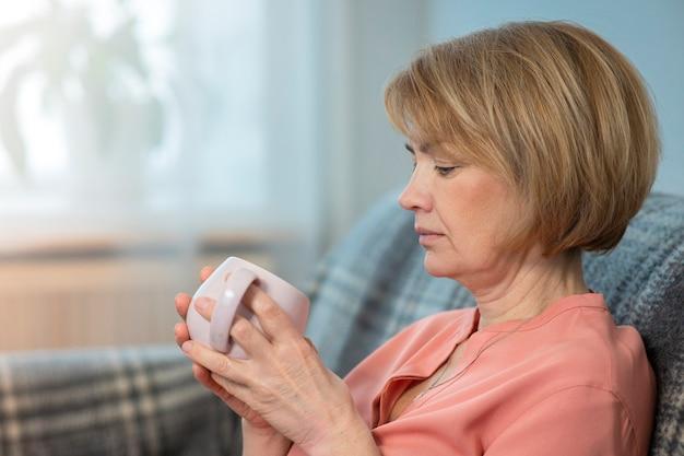 Mooie doordachte peinzende vrouw drinkt thee of koffie uit een kopje thuis op de bank zitten