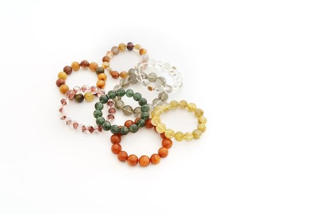 Mooie doorschijnende geassorteerde kleuren rutielkwarts of venusã€â™ haarsteenkraal in armbanden op witte achtergrond