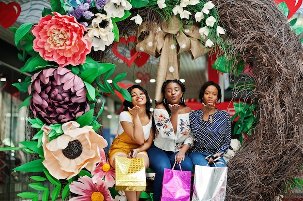 Mooie drie goed geklede afro-amerikaanse meisjes met gekleurde boodschappentassen zittend op de lente decoratie foto zone in winkelcentrum.