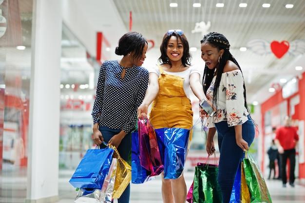 Mooie drie goed geklede afro-amerikaanse meisjesklanten met gekleurde boodschappentassen bij winkelcentrum.