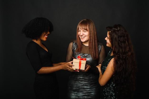 Mooie drie jonge vrouw vreugde terwijl staande met huidige doos tijdens kerstviering.