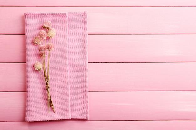 Mooie droge bloemen op servet op houten tafel
