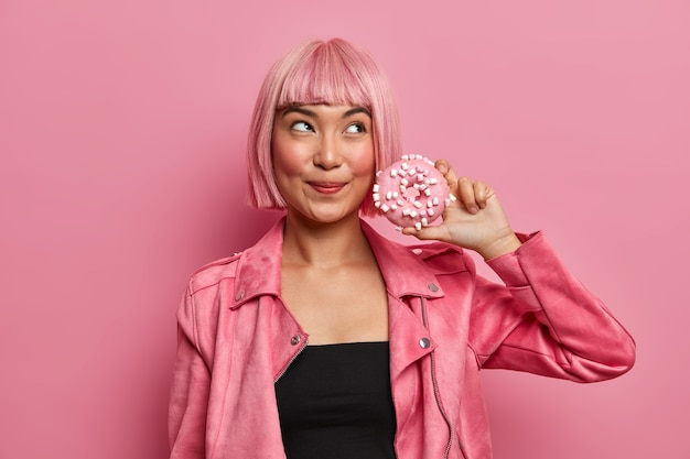 Mooie dromerige dame met bob geverfd haar, houdt heerlijke smakelijke donut heeft de verleiding om een dessert met veel calorieën te eten, draagt een stijlvol roze jasje