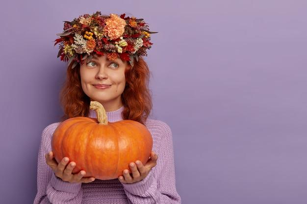 Mooie dromerige vrouw houdt grote rijpe pompoen vast, kijkt bedachtzaam weg, gekleed in oversized trui, kransmodellen tegen paarse muur, kopieerruimte