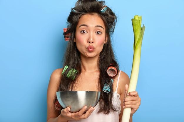 Mooie drukke vrouw houdt lippen rond, houdt stalen kom en verse groene prei vast, houdt zich aan gezond dieet, eet alleen producten met weinig calorieën