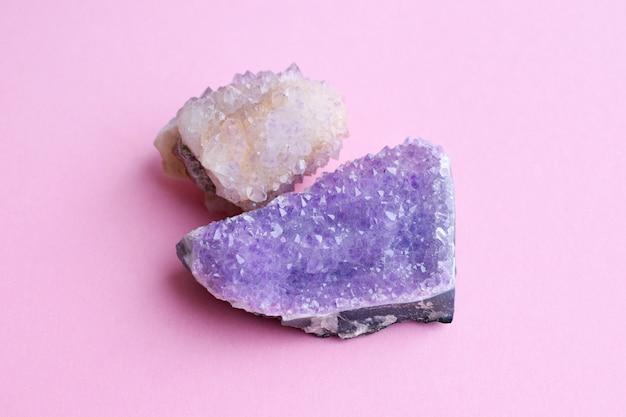 Mooie druse van natuurlijk paars mineraal amethist en cactus amethist kristal op een roze muur. grote kristallen van edelstenen.