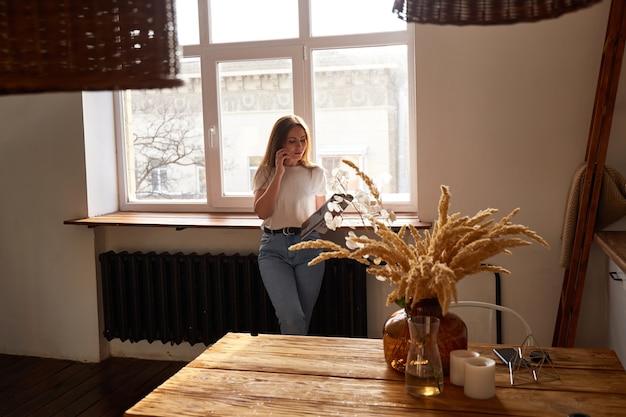Mooie duizendjarige vrouw met behulp van mobiele telefoon en lachend terwijl je in de buurt van keukenraam. natuurlijk ochtendlicht. online chatten of winkelen