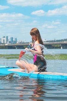 Mooie duizendjarige vrouw op een sup-bord op de rivier