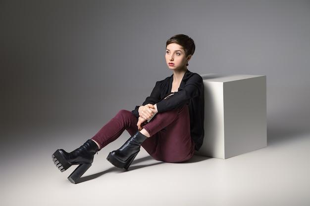 Mooie dunne brunette vrouw zittend op de vloer door kubus haar benen gebogen