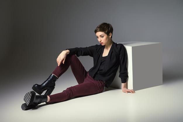Mooie dunne brunette vrouw zittend op de vloer door kubus haar hand op de knie.