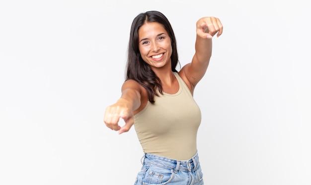 Mooie dunne spaanse vrouw die zich gelukkig en zelfverzekerd voelt en met beide handen naar de camera wijst