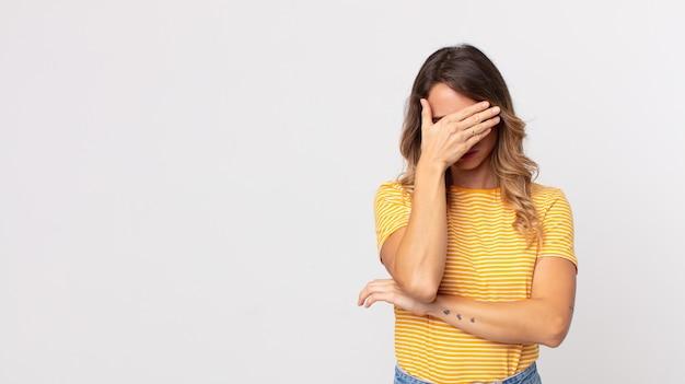 Mooie dunne vrouw die er gestrest, beschaamd of overstuur uitziet, met hoofdpijn, gezicht bedekt met hand