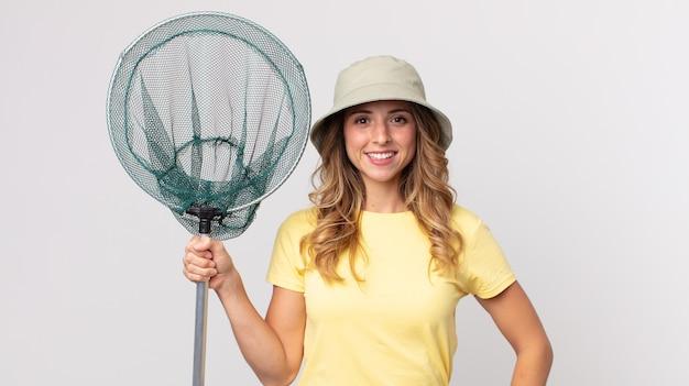 Mooie dunne vrouw die gelukkig lacht met een hand op de heup en zelfverzekerd een hoed draagt en een visnet vasthoudt