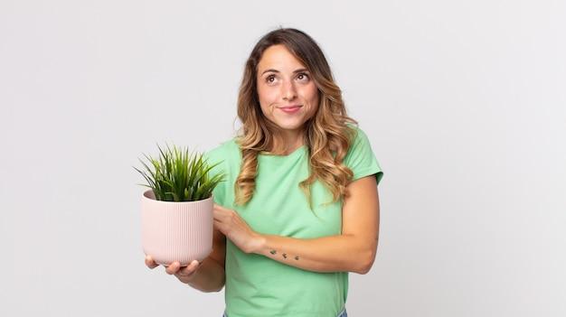 Mooie dunne vrouw die haar schouders ophaalt, zich verward en onzeker voelt en een decoratieve plant vasthoudt