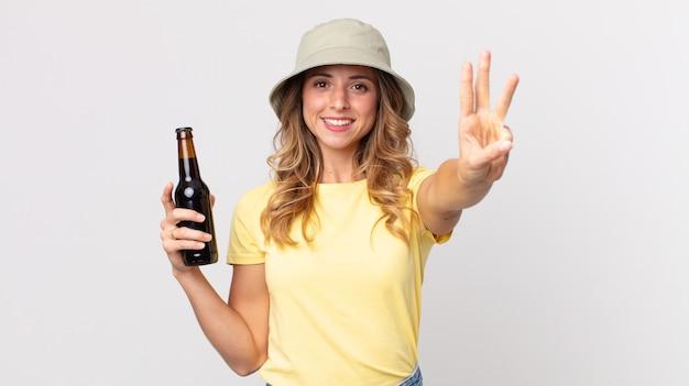 Mooie dunne vrouw die lacht en er vriendelijk uitziet, nummer drie laat zien en een biertje vasthoudt. zomer concept