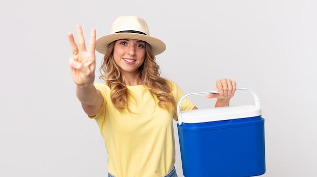 Mooie dunne vrouw die lacht en er vriendelijk uitziet, nummer drie toont en een zomerpicknickkoelkast vasthoudt