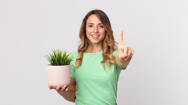 Mooie dunne vrouw die lacht en er vriendelijk uitziet, nummer één toont en een decoratieve plant vasthoudt
