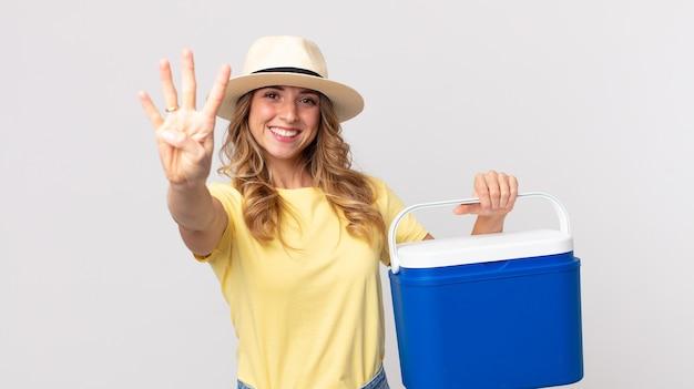 Mooie dunne vrouw die lacht en er vriendelijk uitziet, nummer vier toont en een zomerpicknickkoelkast vasthoudt