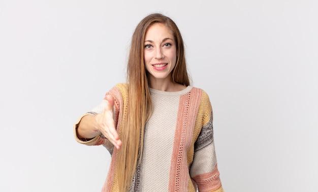 Mooie dunne vrouw die lacht, er gelukkig, zelfverzekerd en vriendelijk uitziet, een handdruk aanbiedt om een deal te sluiten, meewerkt