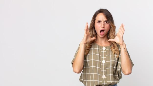 Mooie dunne vrouw die met haar handen in de lucht schreeuwt, zich woedend, gefrustreerd, gestrest en overstuur voelt