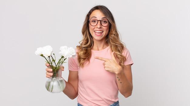 Mooie dunne vrouw die opgewonden en verrast kijkt en naar de zijkant wijst en decoratieve bloemen vasthoudt