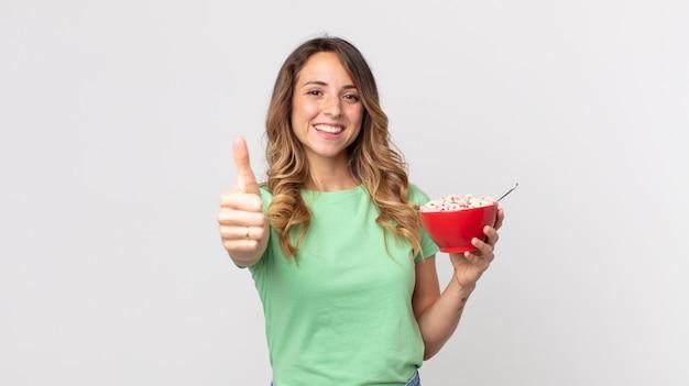 Mooie dunne vrouw die trots is, positief glimlacht met duimen omhoog en een ontbijtkom vasthoudt