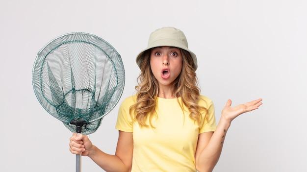 Mooie dunne vrouw die verrast en geschokt kijkt, met open mond terwijl ze een voorwerp vasthoudt met een hoed op en een visnet vasthoudt