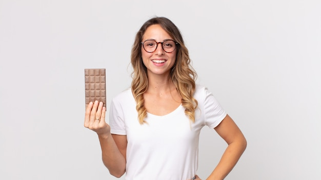 Mooie dunne vrouw die vrolijk lacht met een hand op de heup en zelfverzekerd en een chocoladereep vasthoudt