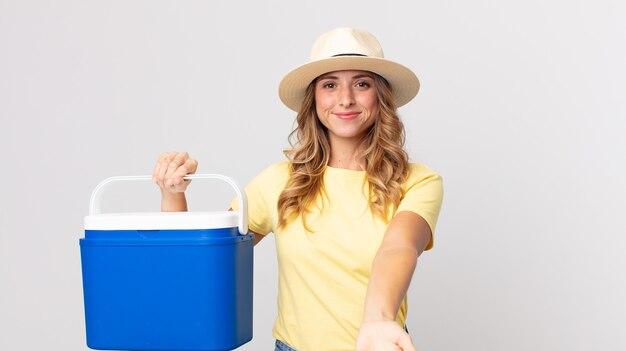 Mooie dunne vrouw die vrolijk lacht met vriendelijk en een concept aanbiedt en toont en een zomerpicknickkoelkast vasthoudt