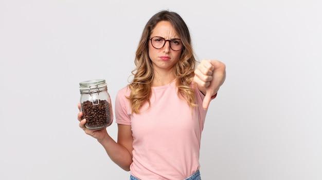 Mooie dunne vrouw die zich boos voelt, duimen naar beneden laat zien en een fles koffiebonen vasthoudt