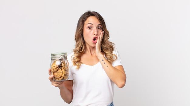 Mooie dunne vrouw die zich gelukkig, opgewonden en verrast voelt en een glazen fles met koekjes vasthoudt