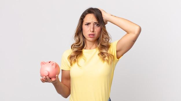Mooie dunne vrouw die zich gestrest, angstig of bang voelt, met de handen op het hoofd en een spaarpotje vasthoudt